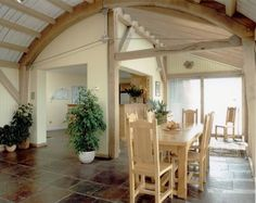 Interior view of Cliffside House in Devon with green oak curved roof and kitchen beyond