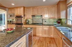 Beautiful kitchen with granite tile counters, center island, stainless steel appliances, double ovens, five burner gas cooktop, and wine fridge! This kitchen has it all! 8522 NE 128th St, Kirkland , 98034