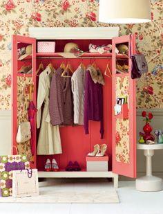 Une armoire revisitée dont les portes et l'intérieur ont été peints en rose et recouverts de papier peint fleuri