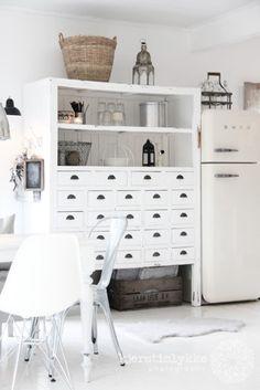 Gezellige witte kast met veel laden naast ivoorkleurige Smeg koelkast.