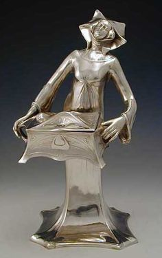 Polished pewter art nouveau figurine holding a jewel casket with hinged lid.  Country of ManufactureGermany  DateC. 1905