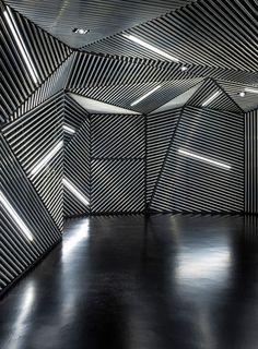 From the visitor's arrival in the lift lobby – an entirely black space pierced only by the RACE signage and an angular arrangement of white lines – the interior is meant to have a disorientating effect.
