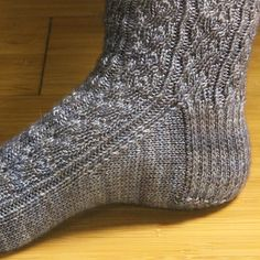 This sock uses a simple pattern that is reminiscent of rain running down a window. Texture is created using center double decreases and yarn overs. Some ribbing is incorporated into the design to give the sock stretch. This top down design uses a standard heel flap construction and ends with a simple rounded toe.