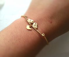 Click here below to view this bracelet http://www.storenvy.com/products/14286789-gold-love-birds-initials-bracelet-baby-bird-bracelet-personalized-initials-b This little bracelet has a matte gold kissing love birds branch and a tiny baby bird hanging below on the branch. Each bird has a hand stamped engraved letter initial, the baby bird is left blank in the photos but can have a letter initial on it also. Matte gold love birds bracelet connects to a ...