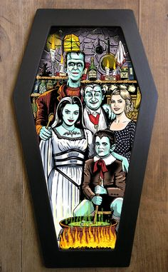 A monstrous illustration inspired by The Munsters in a coffin-shaped frame. Each illustration is framed with a handmade one piece wood frame painted in matte black. The front panel is made from clear acrylic and the back is made from a resistant cardboard in black, supported by a single