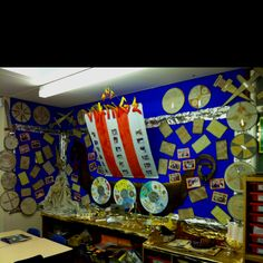Viking display - natural tye dye, group designed shields, photos of dressing up Viking day, pattern weapons, clay runes, kennings poems about longships and boats made to experiment floating and sinking in science. (by Sally Maddison)