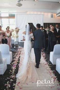 Indoor wedding ceremony at Dockside, L'Aqua - Terrace Room. Ceremony decorations included white carpet runner, aisle rose petals and white chiffon canopy with fresh flowers. #weddingcanopy #weddingflowers