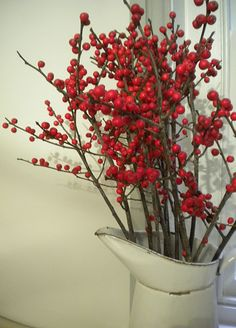 red berry branches in tall skinny glass vases