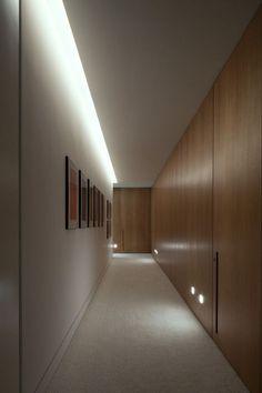 Puerta suelo-techo, panelado de madera, iluminación de paso.