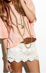 Loose, Baby Pink Shirt; With An Off White Laced Skirt, Around The Waist A Simple Brown Belt; Paired With Gold, Rustic Jewelry.
