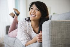 Pacific Islander woman laying on sofa by Gable Denims