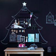 Ein Weihnachtsbaum, der auf eine mit schwarzer Tafelfarbe gestrichene Wand gemalt wurde. RIBBA Bilderleisten in Schwarz und eine schwarze FINTORP Stange befinden sich im Baum und wurden mit Backbüchern, Backutensilien, Plätzchen und Muffins geschmückt.