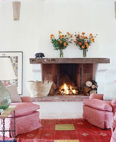 wooden mantel, simple rustic chic, pink slipcovered chairs, vintage rug, glass lamp
