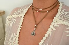 Item details: Its an one of a kind wrap leather choker made with either black or brown genuine leather on one side and suede on the other side of the cord and a unique geometric coin pendant is placed at the centre and and silver barrel and flat bead spacers around the neck. Its