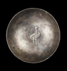 A Sasanian silver bowl  Iran, circa 6th-7th Century A.D. The hemispherical shallow bowl decorated on the inside with a peacock, the body mould in relief with added incised decoration, with long tail feathers and scarf around its neck, 5¾in (14.5cm) diam