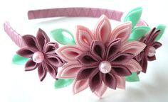 A flowers are made in the technique of tsumami kanzashi.  Plastic headband is weaved with satin ribbon.  Flowers are made from grosgrain ribbons. At your