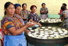 mujeres haciendo tortillas al comal  Homemade corn tortillas on the cast iron griddle.