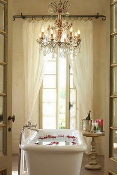 the bath, with the neutral curtains and doors and that lovely, glamourous chandelier