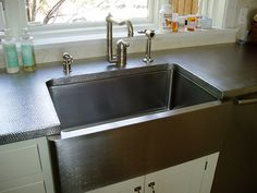 Hammered stainless steel countertop with undermount farm sink.