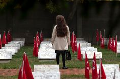 A child of the Turkish community stands between graves at the Turkish Heroes cemetery in Bucharest, Romania, Tuesday, Oct. 15, 2013 after Ei...