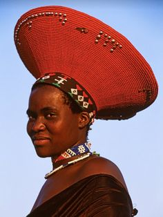 "Africa | A Zulu bride wears a flaring red headdress reminiscent of the hairstyle of her ancestors.  This traditional headdress was originally made from her mother's hair and received as a gift on the day of her marriage.  South Africa, 1996, | ©Carol Beckwith & Angela Fisher. Publication ""African Ceremonies"""