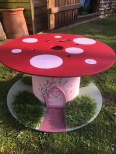 Toadstool cable reel, glitter added to spots for added sparkle. Fairy door added and some AstroTurf for grass.