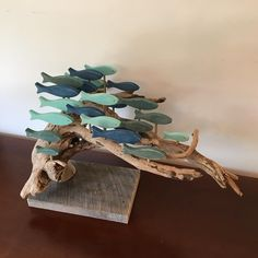 A large school of fish on an inverted driftwood root ball. Teal, aqua and royal blue fish are featured. Driftwood Fish, Driftwood Projects, Wooden Fish, Glass Garden Art, Ribbon Sculpture, Fish Design, Shell Crafts, Fish Art, Nature Crafts