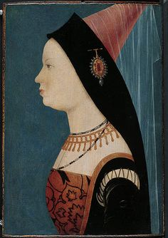 Mary of Burgundy, Tyrol(?) circa 1528-EXCERPT: She wears a tall Burgundian hennin, or steeple headdress, characteristic of 1470s fashion. The heavy band of material over her forehead is pinned to the base of the conical headdress by a distinctive agrafe (ornamental clasp).