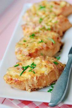 Bereiden: Snij de stokbrood in 12 dikke plakken en leg ze op een bakplaat. Meng in een kom de yoghurt met de gesmolten boter en crème fraiche. Breng dit op smaak met een snufje zout, peper en de paprikapoeder. Voeg de fijngesneden ham en bieslook toe. Roer de geraspte kaas erdoor. Verdeel het ham en kaas mengsel over de stokbroodjes.