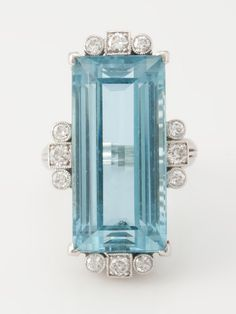 Vintage Platinum Aquamarine and diamond ring, Vintage platinum Aquamarine & diamond ring. ~ Circa: late 1940's early 1950's. Exquisite platinum ring is approx. 18 carat rectangular step cut Aquamarine. Enhanced with 12 side-stone diamonds. Combination bead set and bezel set, with mil-grain finish. USD 8,800
