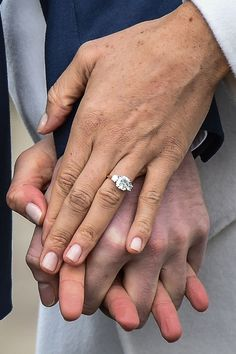 """Meghan Markle's engagement ring features a cushion-cut stone in the center, sourced from Botswana, in honor of Harry and Meghan's special getaway trip together. The diamond is flanked by two smaller round-cut stones from Princess Diana's jewelry collection """"to make sure she's with us on this crazy journey together,"""" Harry said. The stones are set on a yellow gold band—Meghan's favorite. The ring is said to be worth $1 million dollars because of its Royal connection."""