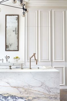This dichotomy is so good. Marble and crown with panel molding with an industrial light fixture and kitchen hardware.