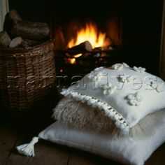 Pile of neutral embroidered cushions in front of a lit log fire in a living room
