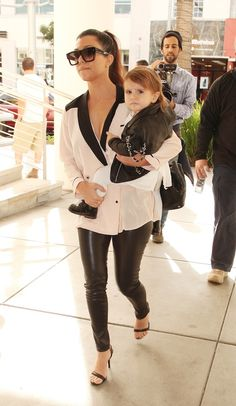 Style inspirations via modern mommy Kourtney Kardashian.  Kourtney is wearing an ASOS tuxedo top, Alice and Olivia leather leggings from DASH, Alexander Wang shoes, Chanel backpack, and Dita sunglasses from DASH. Penelope is wearing a jacket by Kanna Inc, a Bonpoint dress, Runway tights, and Bonpoint boots.