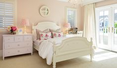 Elegant girl's bedroom designed for coastal living. Barclay Butera Interiors, Pink wall paint, pink bedroom, white headboard and bed frame, pink lamps