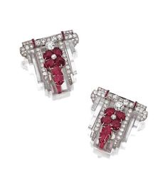 PAIR OF ART DECO CARVED RUBY, DIAMOND AND ROCK CRYSTAL CLIPS, CIRCA 1925.  Of geometric design, the carved rock crystal plaques of stepped outline decorated with clusters of carved ruby leaves, further set with 102 round and single-cut diamonds weighing approximately 6.00 carats, and with bands of calibré-cut rubies, mounted in platinum.