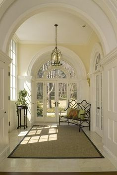 Gorgeous arches, windows, and light in this back foyer leading out towards the backyard. Pale yellow walls enhance the feeling of sunny airiness, and that black bench is the perfect grounding foil. A beautiful hallway. House Design, Future House, House, Home, Entry Foyer, Windows And Doors, House Styles, New Homes, Stairways
