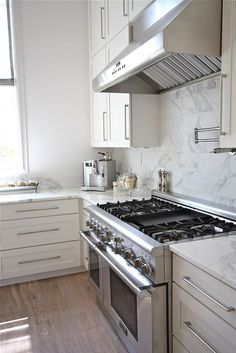 white cabinets + wood floor + marble