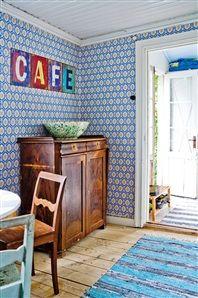 """Den gamla skänken har haft  sin plats sedan huset byggdes.  Trasmattor, Ikea.  """"Café""""-skylt, Magasinet  i Waxholm."""