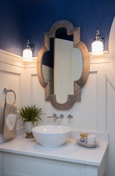 The wallcovering in the powder room is a grasscloth from Duralee. The weathered mirror is from Tradewinds. The countertop is Caesarstone organic white. Beachy without Kitschy! An elegant WaterColor, Florida beachouse on www.StyleBlueprint.com