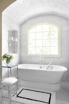 Clean white bathroom. Floor to ceiling tile + free standing tub + basket-weave