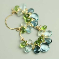 My gemstone weave hoop earrings are reinterpreted in bright blue and green gemstones. I've interlaced swiss blue topaz, london blue, sky blue, peridot, aquamarine and prehnite with fine gauge gold fill wire to form my original gem weave hoops. These are pure glam! Earrings measure 1 1/2 by 1 1/2 inches.
