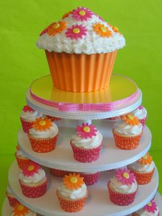 Spring themed Giant cupcake with candy shell and pink and orange daisies, with coordinating cupcakes and liners.