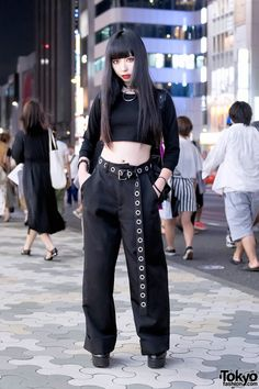 Katorina is wearing a black long sleeve crop top from American Apparel with Faith Tokyo pants and resale platform shoes. Accessories – some of which came from Deandri – include a large o-ring choker, a black grommet belt, several bracelets, and a Killstar backpack.