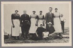 Groep van tien mensen, twee mannen, zes vrouwen en twee kinderen poserend in Urker dracht, met de zee op de achtergrond. 1920-1930 #Urk