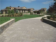 The low walls bordering this driveway guide the eye towards the destination. Design by Roger Haywood of Accent Landscapes. See more from this Colorado Tuscan landscape here http://www.landscapingnetwork.com/colorado/colorado-springs-tuscan.html