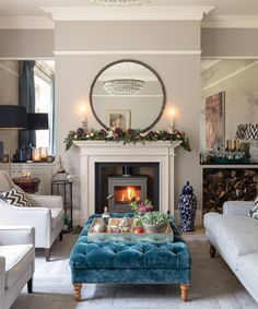 A teal ottoman adds sumptuous colour, while mirrored inserts either side of the fireplace amplify the sense of light and space. A large circular mirror above the fireplace adds a modern element in this other traditional space. Classic Living Room, Home Living Room, Living Room Designs, Living Room Decor, Modern Living, Living Room Flooring, Living Room Furniture, Mirror Above Fireplace, English Country Decor