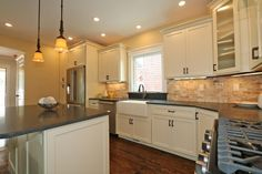 Eastman St. Woodworks Kitchen Cabinets. Kitchen designed by John Brassinton at New England Building Supply in Boston, MA. Door style is Salem and the color is Sherwin Williams' Navajo White. #eastmanstwoodworks #whitekitchen #kitchendesign.