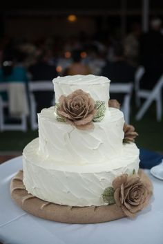 three tiered white wedding cake with burlap flowers