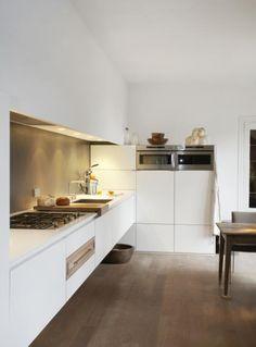 ... mooi, deze combinatie van een zwevende witte keuken met bruine vloer